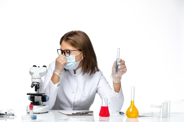 Vooraanzicht vrouwelijke arts in medisch pak met masker vanwege covid werken met oplossingen op lichte witte ruimte