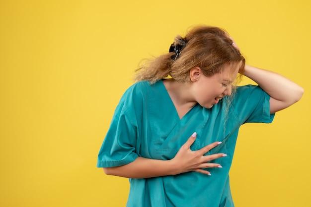 Vooraanzicht vrouwelijke arts in medisch shirt die aan hartpijn lijdt, medic covid-19 verpleegkundige kleur gezondheid