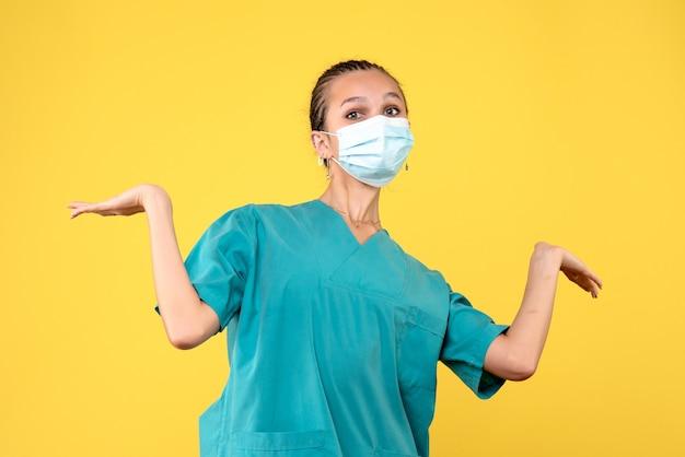 Vooraanzicht vrouwelijke arts in medisch shirt en masker, gezondheidsverpleegkundige virus pandemie ziekenhuis covid-