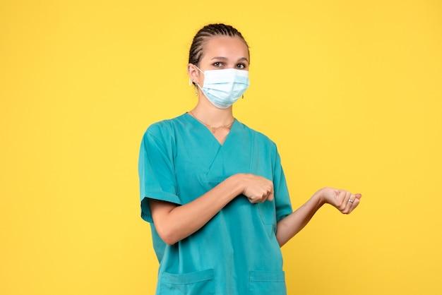 Vooraanzicht vrouwelijke arts in medisch shirt en masker, pandemische medic gezondheidsverpleegkundige virus covid-