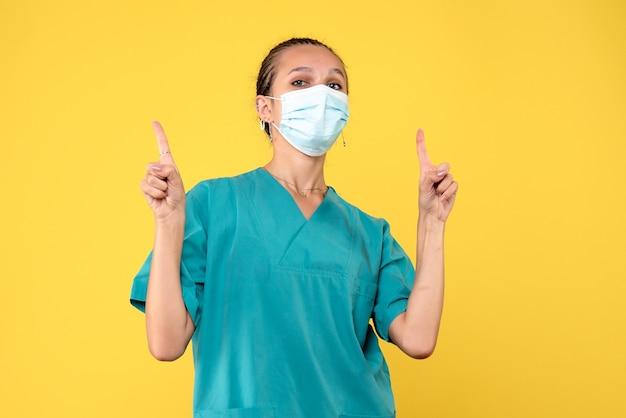 Vooraanzicht vrouwelijke arts in medisch shirt en masker, verpleegkundige pandemie ziekenhuis virus gezondheid covid-