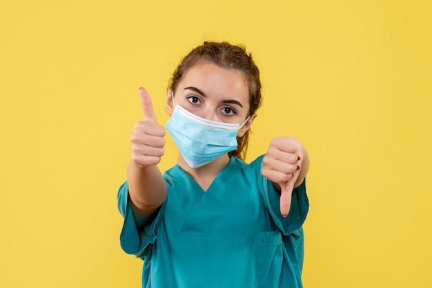 Vooraanzicht vrouwelijke arts in medisch shirt en masker, virus pandemie uniform covid-19 gezondheid coronavirus