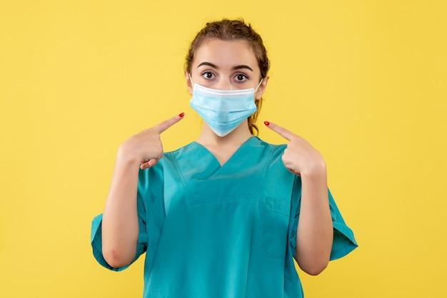 Vooraanzicht vrouwelijke arts in medisch shirt en steriel masker, coronavirus uniform virus covid-19 pandemische gezondheid