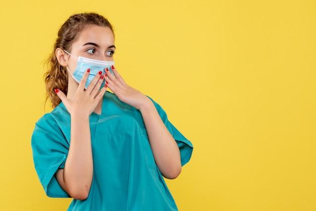 Vooraanzicht vrouwelijke arts in medisch shirt en steriel masker, uniform virus covid-19 coronavirus pandemie gezondheid
