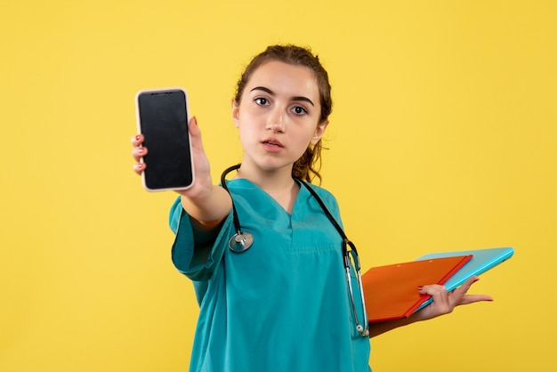 Vooraanzicht vrouwelijke arts in medisch shirt met notities en telefoon, gezondheid emotie uniform pandemisch covid-19-virus