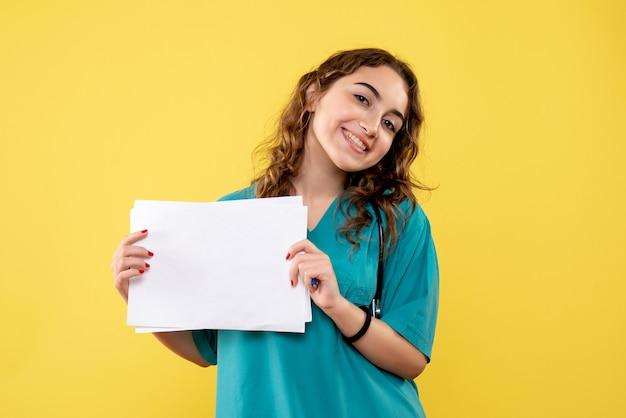 Vooraanzicht vrouwelijke arts in medisch shirt met papieren analyse, gezondheidsvirus uniform covid-19 pandemische emotie