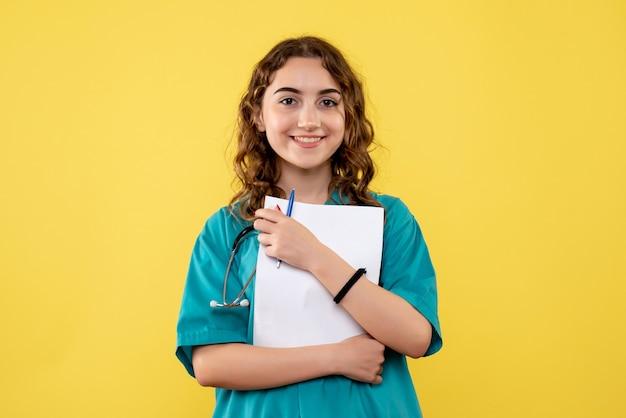 Vooraanzicht vrouwelijke arts in medisch shirt met papieren analyse, gezondheidsvirus uniforme covid-19 pandemische emoties