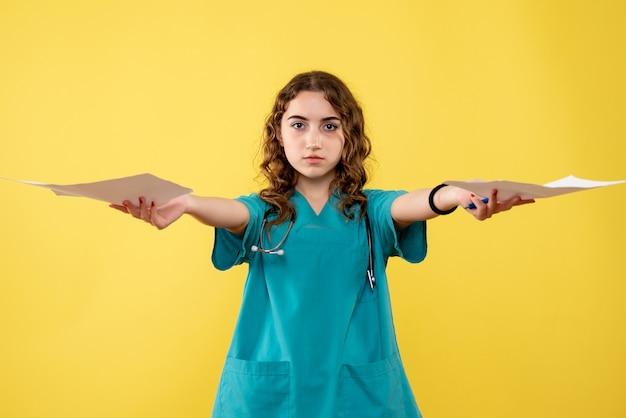 Vooraanzicht vrouwelijke arts in medisch shirt met papieren analyse, pandemie gezondheidsvirus uniform covid-19 emotie