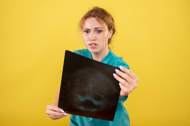 Vooraanzicht vrouwelijke arts in medisch shirt met röntgenfoto, kleur covid-19 gezondheid emotie pandemisch virus