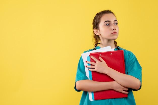 Vooraanzicht vrouwelijke arts in medisch shirt met verschillende notities, kleur pandemie virus gezondheid emotie covid-19 uniform