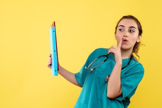 Vooraanzicht vrouwelijke arts in medisch shirt met verschillende notities, kleur virus gezondheid emotie covid-19 pandemie