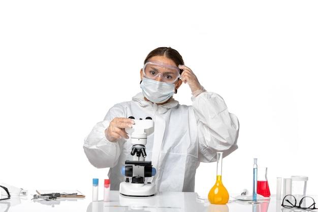 Vooraanzicht vrouwelijke arts in speciaal pak en het dragen van masker werken met microscoop op een lichtwitte achtergrond virus covid pandemie coronavirus