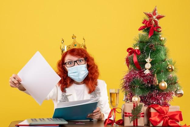 Vooraanzicht vrouwelijke arts in steriel masker documenten controleren