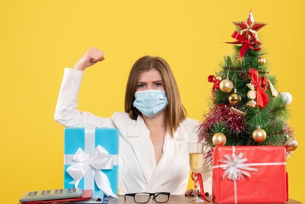 Vooraanzicht vrouwelijke arts in steriel masker met cadeautjes