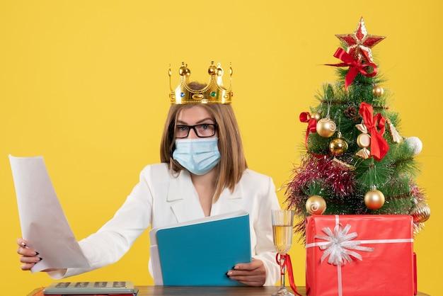 Vooraanzicht vrouwelijke arts in steriel masker met documenten