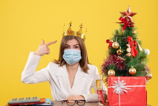 Vooraanzicht vrouwelijke arts in steriel masker met kroon