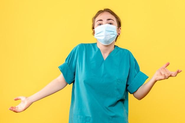 Vooraanzicht vrouwelijke arts in steriel masker op een gele achtergrond pandemisch virus covid gezondheid