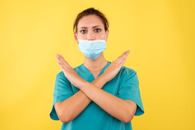 Vooraanzicht vrouwelijke arts in steriel masker op geel bureau verpleegster virus gezondheid medic ziekenhuis ziekte emotie