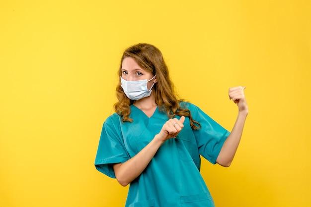Vooraanzicht vrouwelijke arts in steriel masker op gele ruimte