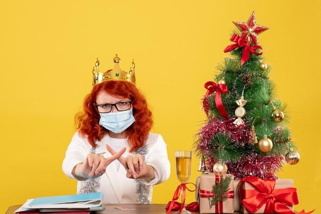 Vooraanzicht vrouwelijke arts in steriel masker rond kerstcadeautjes
