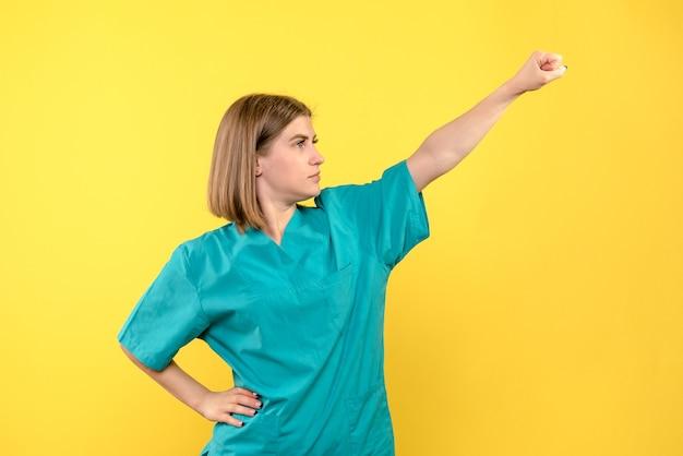Vooraanzicht vrouwelijke arts in superman pose op gele ruimte