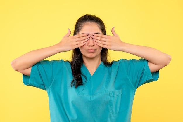 Vooraanzicht vrouwelijke arts in uniform die haar ogen bedekt met handen
