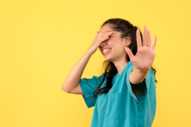 Vooraanzicht vrouwelijke arts in uniform die haar staande ogen bedekt