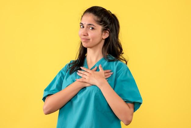 Vooraanzicht vrouwelijke arts in uniform handen zetten
