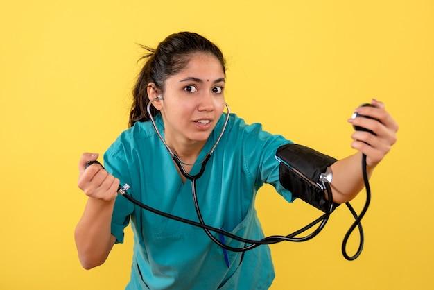 Vooraanzicht vrouwelijke arts in uniform houden bloeddrukmeetapparaat