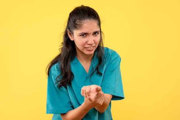 Vooraanzicht vrouwelijke arts in uniform met haar arm staande