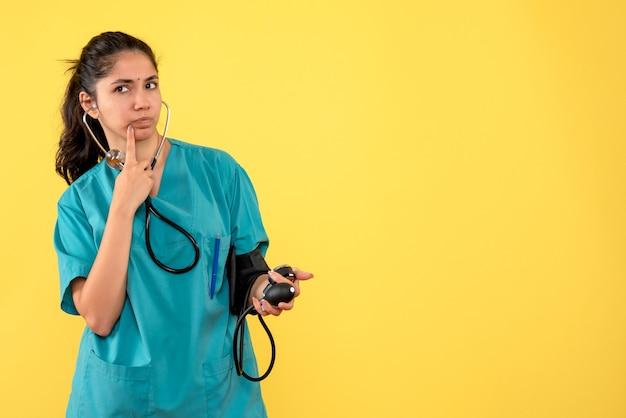 Vooraanzicht vrouwelijke arts in uniforme bedrijf bloeddrukmeters staan