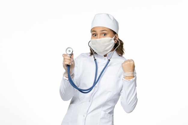 Vooraanzicht vrouwelijke arts in wit medisch pak en masker met behulp van stethoscoop op de witte muur pandemy virussen ziekte geneeskunde