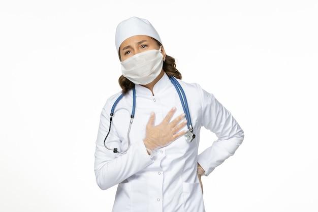 Vooraanzicht vrouwelijke arts in wit medisch pak en masker met hartzeer op witte muur pandemy virus ziekte ziekte geneeskunde