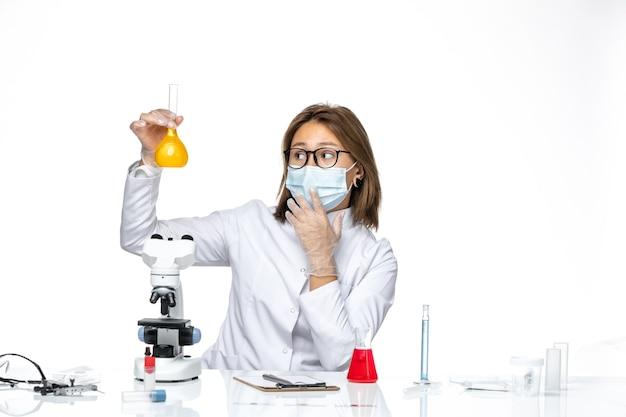 Vooraanzicht vrouwelijke arts in wit medisch pak en masker vanwege coronavirus die met oplossingen op witte ruimte werkt