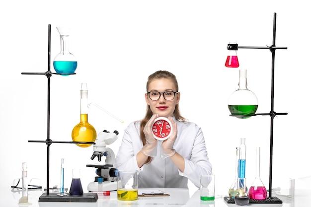 Vooraanzicht vrouwelijke arts in wit medisch pak klokken te houden en glimlachend op witte achtergrond virus covid chemie pandemie
