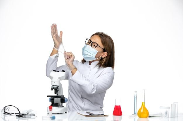 Vooraanzicht vrouwelijke arts in wit medisch pak masker en handschoenen dragen vanwege covid op witte ruimte