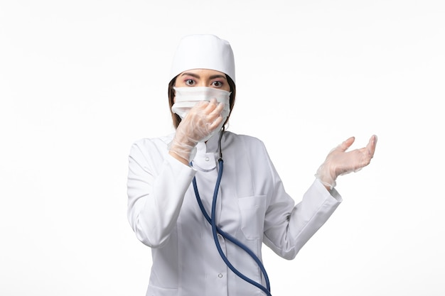 Vooraanzicht vrouwelijke arts in wit medisch pak met een masker vanwege pandemie op witte muur ziekte gezondheid geneeskunde pandemie covid-