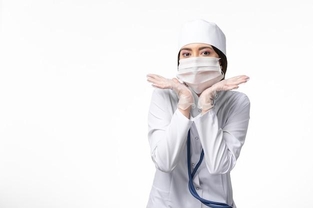 Vooraanzicht vrouwelijke arts in wit medisch pak met een masker vanwege pandemie poseren op witte muur gezondheid geneeskunde pandemie covid-