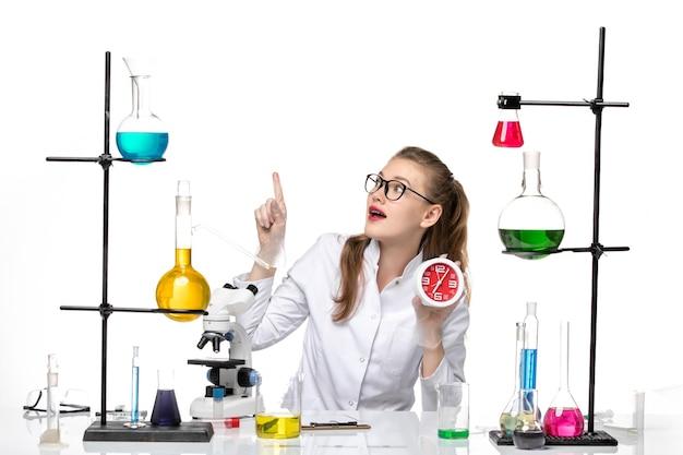 Vooraanzicht vrouwelijke arts in wit medisch pak met klokken op lichte witte achtergrond virus chemie pandemie covid