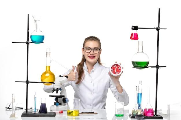 Vooraanzicht vrouwelijke arts in wit medisch pak met klokken op lichte witte achtergrond virus covid chemie pandemie