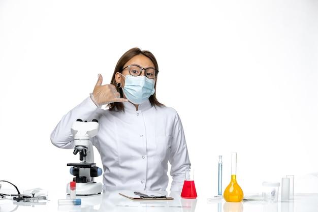 Vooraanzicht vrouwelijke arts in wit medisch pak met masker en handschoenen vanwege covid poseren op witte ruimte