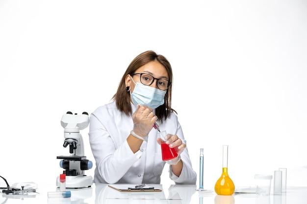 Vooraanzicht vrouwelijke arts in wit medisch pak met masker vanwege covid in werkproces op de lichte witte ruimte Gratis Foto