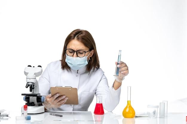 Vooraanzicht vrouwelijke arts in wit medisch pak met masker vanwege covid in werkproces op witte ruimte