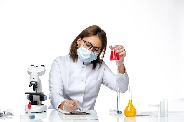 Vooraanzicht vrouwelijke arts in wit medisch pak met masker vanwege covid notities schrijven over licht-witte ruimte