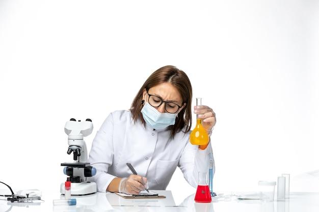 Vooraanzicht vrouwelijke arts in wit medisch pak met masker vanwege covid schrijven op lichte witte ruimte
