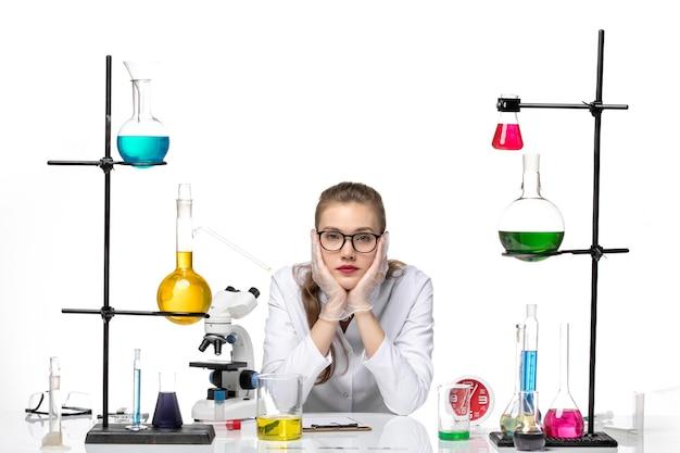 Vooraanzicht vrouwelijke arts in wit medisch pak zit aan tafel met oplossingen die zich vervelen op witte achtergrond covid pandemisch chemievirus
