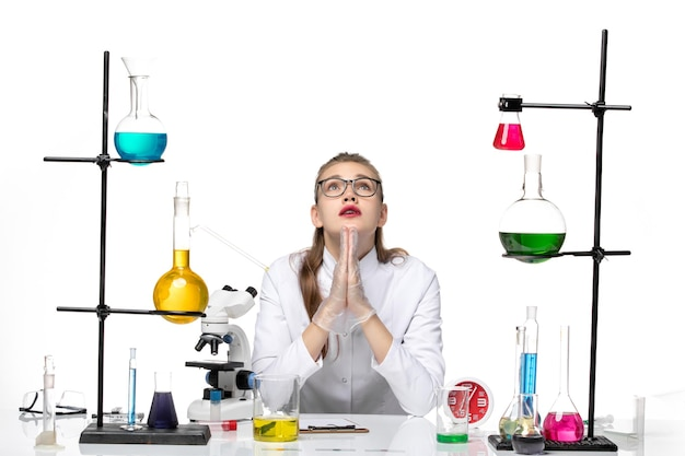 Vooraanzicht vrouwelijke arts in wit medisch pak zit tafel met oplossingen bidden op witte achtergrond covid chemie virus pandemie
