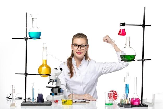 Vooraanzicht vrouwelijke arts in wit medisch pak zit tafel met oplossingen buigen op witte achtergrond covid chemie virus pandemie