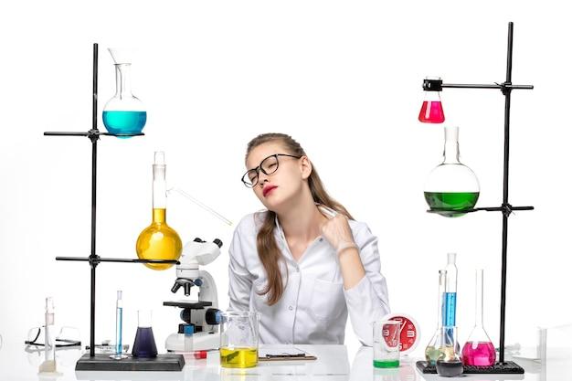 Vooraanzicht vrouwelijke arts in wit medisch pak zit tafel met oplossingen moe voelen op witte achtergrond virus covid pandemie chemie