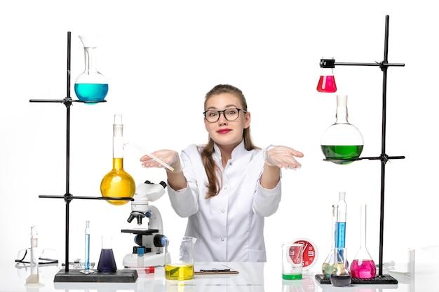 Vooraanzicht vrouwelijke arts in wit medisch pak zit tafel met oplossingen op de witte achtergrond virus covid pandemie chemie